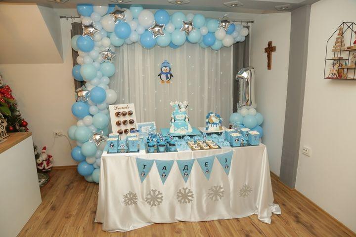 Зимска декорација со балони и слатка маса за прв роденден